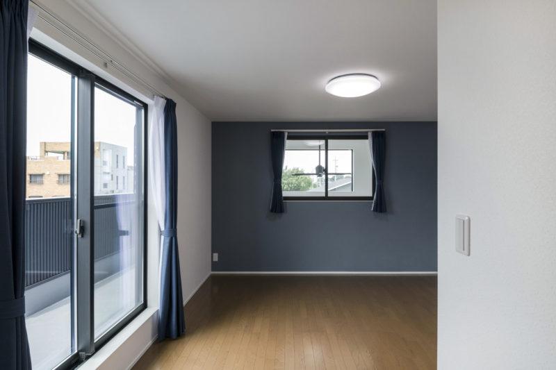 吹抜けの室内窓で明るい寝室
